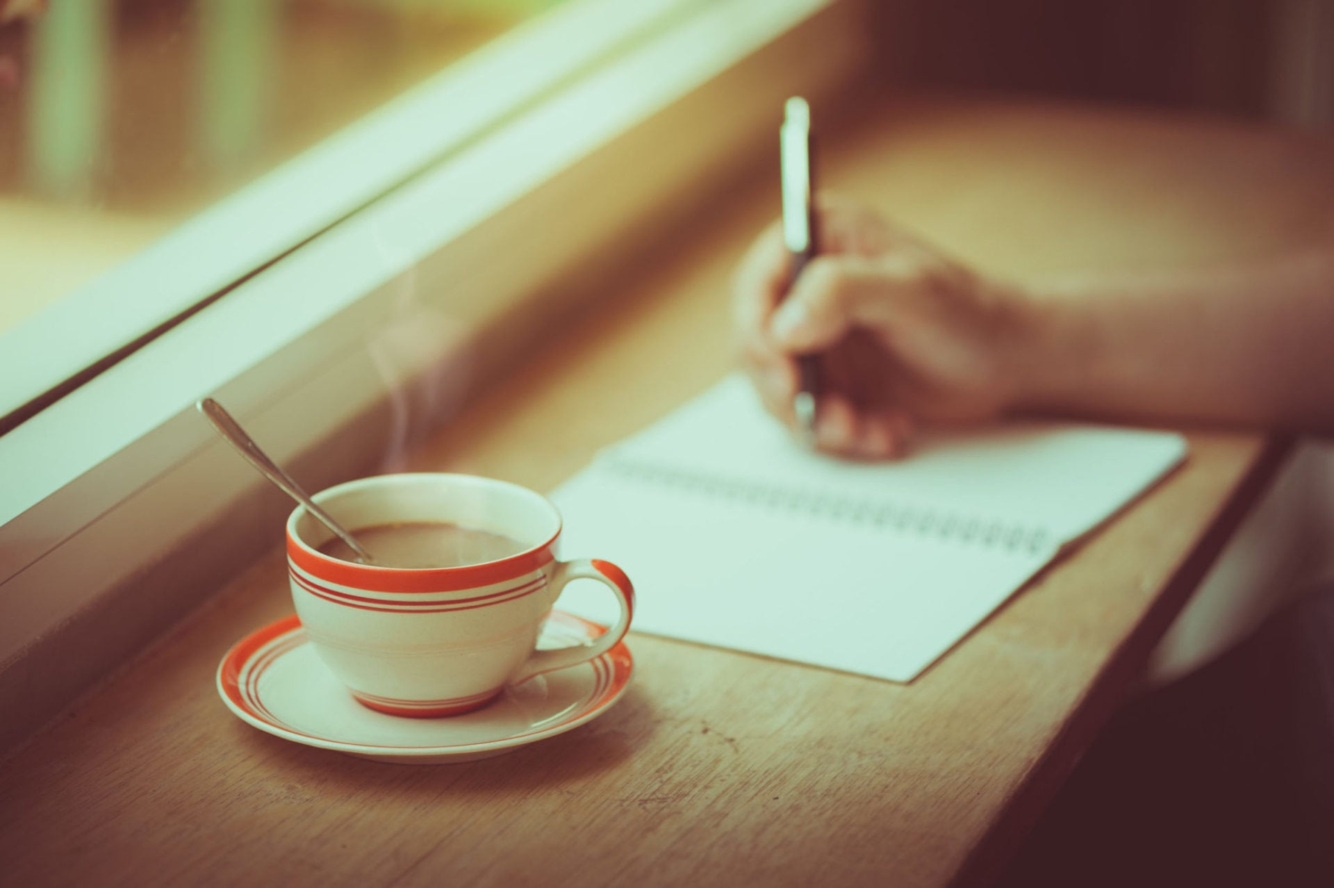 48726072 - a coffee cup on wood bar beside window in cafe with male right hand writing on notebook in morning time with vintage film filter effect